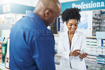 Buy stock photo Shot of a female pharmacist assisting a customer in a drugstore