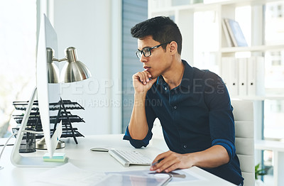 Buy stock photo Shot of a young businessman using a computer at his desk in a modern office
