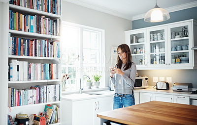 Buy stock photo Cropped shot of a woman using her cellphone at home