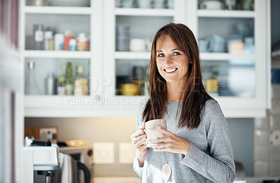 Buy stock photo Cropped shot of a woman holding a cup of coffee while relaxing at home