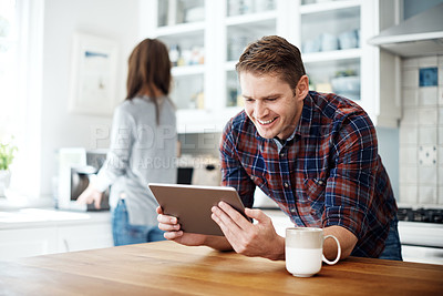 Buy stock photo Shot of a man using a digital tablet with his girlfriend standing in the background