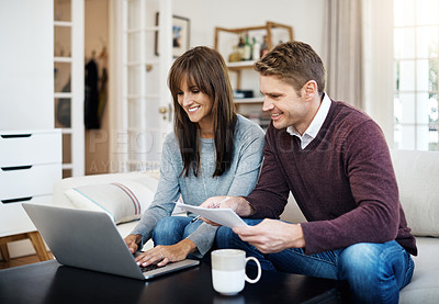 Buy stock photo Shot of a couple using a laptop while working on paperwork