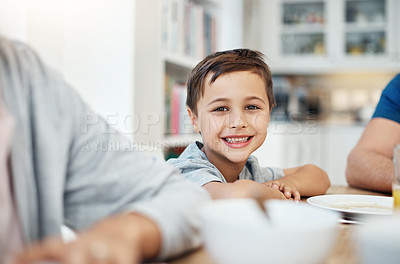 Buy stock photo Cropped shot of a young boy sitting at the breakfast table