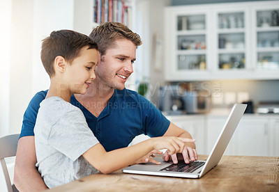 Buy stock photo Shot of a man using a laptop while sitting with his son