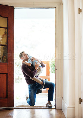 Buy stock photo Shot of a little boy running into his father's arms as he arrives at home