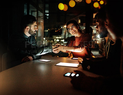 Buy stock photo Shot of a young businessman and businesswoman shaking hands during a meeting with colleagues during a late night at work