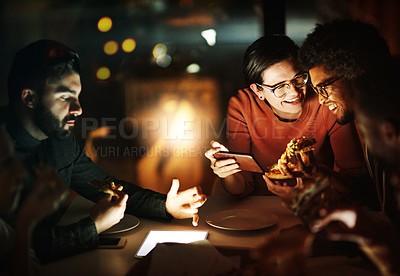 Buy stock photo Shot of a group of young businesspeople having pizza during a late night meeting at work