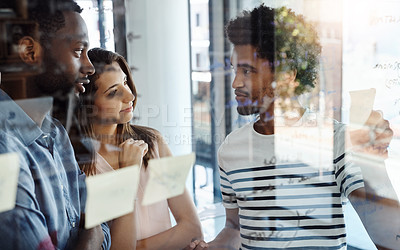 Buy stock photo Shot of a group of young designers brainstorming with notes on a glass wall in an office