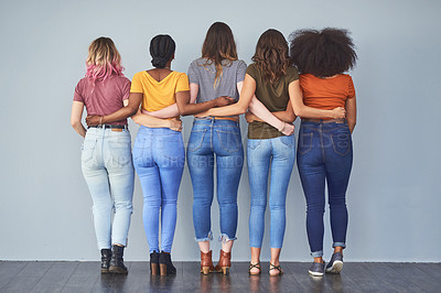 Buy stock photo Rearview studio shot of a group of young women embracing against a gray background