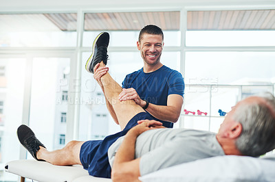 Buy stock photo Cropped shot of a handsome young male physiotherapist doing a consultation and assessment with a senior patient