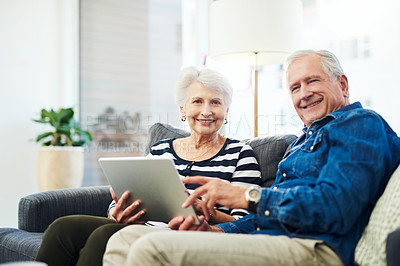 Buy stock photo Portrait of senior couple using a digital tablet together on the sofa at home