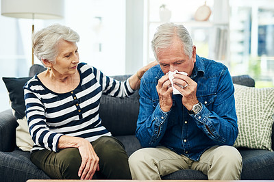 Buy stock photo Shot of a senior man blowing his nose with his wife comforting him on the sofa