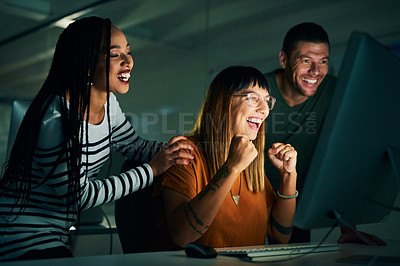 Buy stock photo Cropped shot of three creative business colleagues cheering while working on a computer late at night in their office