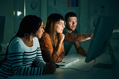 Buy stock photo Cropped shot of three creative business colleagues working on a computer late at night in their office
