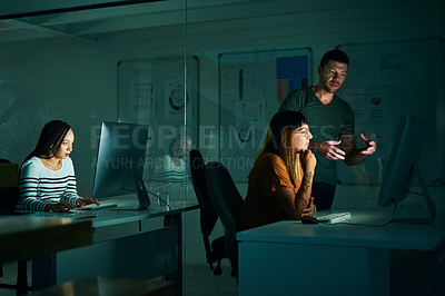Buy stock photo Cropped shot of two creative business colleagues working on a computer late at night in their office