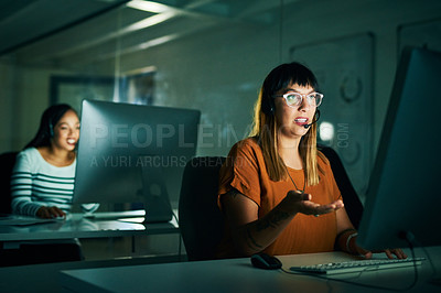 Buy stock photo Cropped shot of an attractive young female call center agent working late at night in her office