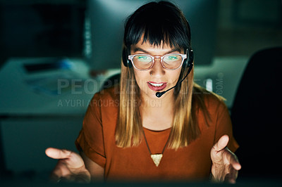 Buy stock photo High angle shot of an attractive young female call center agent working late at night in her office