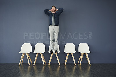 Buy stock photo Studio shot of a handsome businessman standing on a chair while  waiting in line for an interview against a grey background