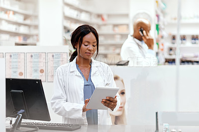 Buy stock photo Cropped shot of an attractive young female chemist working behind a counter in the pharmacy with a colleague in the background