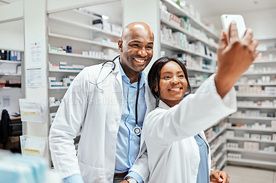Buy stock photo Cropped shot of two young chemists taking selfies while working in the pharmacy