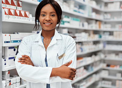 Buy stock photo Cropped portrait of an attractive young female chemist standing with her arms folded in the pharmacy