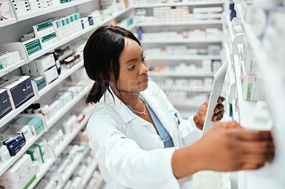 Buy stock photo High angle shot of an attractive young female chemist doing stock take while working in the pharmacy