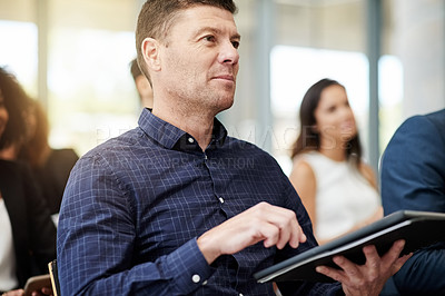 Buy stock photo Shot of a businessman using a digital tablet during a conference