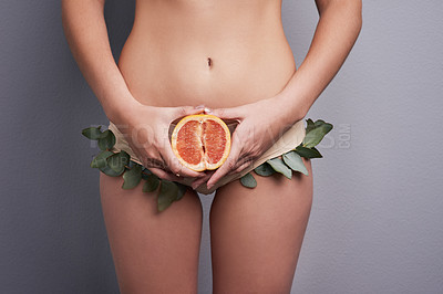 Buy stock photo Cropped studio shot of a woman wearing leafy underwear and holding a grapefruit against a grey background