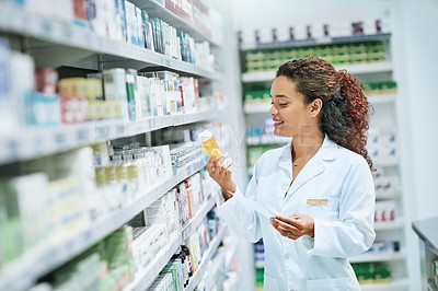 Buy stock photo Shot of a young woman filling a prescription while working in a chemist