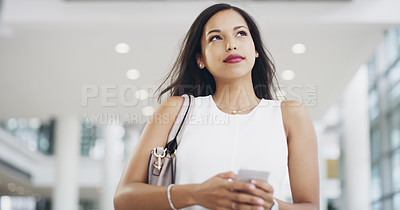 Buy stock photo Cropped shot of a young businesswoman using a smartphone while walking through a modern office