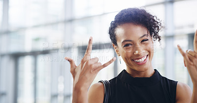 Buy stock photo Cropped shot of a young businesswoman showing a rock 'n roll sign while walking through a modern office