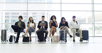 Buy stock photo Full length shot of a group of businesspeople sitting in an airport waiting room