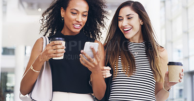 Buy stock photo Cropped shot of two young businesswomen chatting and using a smartphone while walking in an office on a coffee break