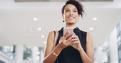 Buy stock photo Cropped shot of a young businesswoman using a smartphone and waving while walking through a modern office