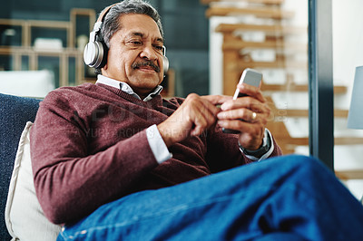 Buy stock photo Cropped shot of a mature man wearing headphones while relaxing at home