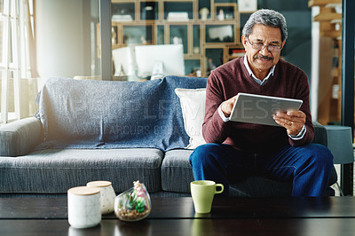 Buy stock photo Cropped shot of a mature man using his digital tablet while relaxing at home