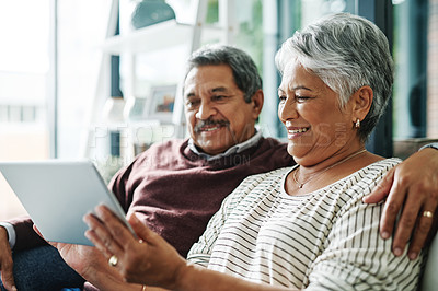 Buy stock photo Shot of a mature couple using a digital tablet while relaxing at home