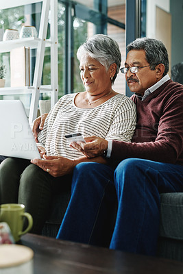Buy stock photo Shot of a mature man holding up a card while browsing with his wife online