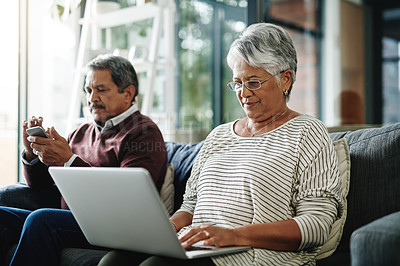 Buy stock photo Shot of a mature woman woman using a laptop while her husband sits in the background
