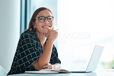Buy stock photo Cropped portrait of a happy young businesswoman working on a laptop in an office
