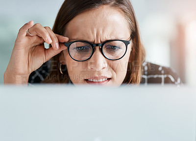 Buy stock photo Cropped shot of a young businesswoman looking confused while working on a laptop in an office