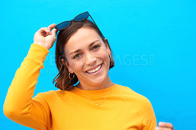 Buy stock photo Cropped portrait of a happy young woman posing against a blue background