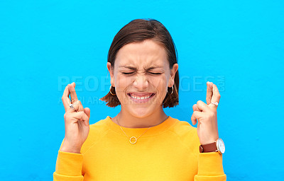Buy stock photo Cropped shot of a young woman crossing fingers against a blue background