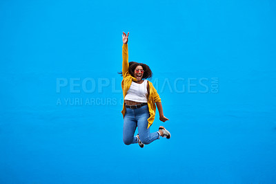 Buy stock photo Full length shot of a happy young woman jumping into the air against a blue background