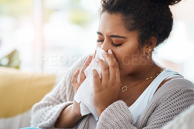 Buy stock photo Cropped shot of a young woman blowing her nose with a tissue at home