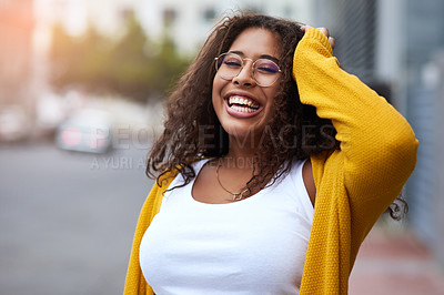 Buy stock photo Cropped portrait of a happy young woman standing outdoors in an urban setting