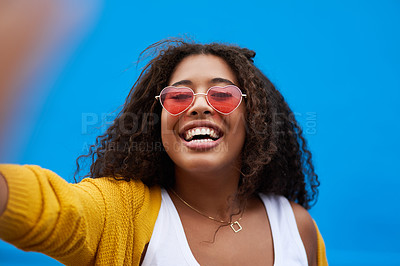 Buy stock photo Cropped portrait of a happy young woman taking a selfie against a blue background