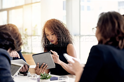 Buy stock photo Shot of a young businesswoman using a digital tablet during a meeting in an office