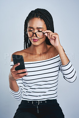 Buy stock photo Studio shot of a young woman reading something on her cellphone