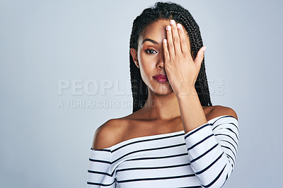 Buy stock photo Shot of a beautiful young woman covering her eye against a grey background